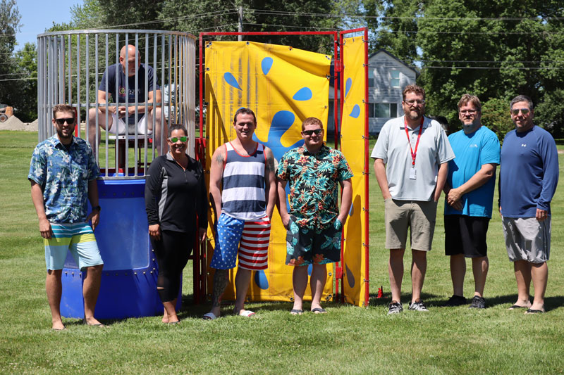 Geater employees having fun at company party in front of water dunk tank